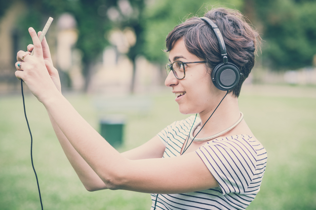 young hipster woman listening to music selfie