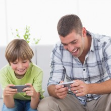 Happy father and son playing games on mobile phone at home